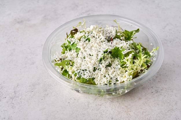 Salade van verse groenten met kaas in doorzichtige plastic container designer food concept voor