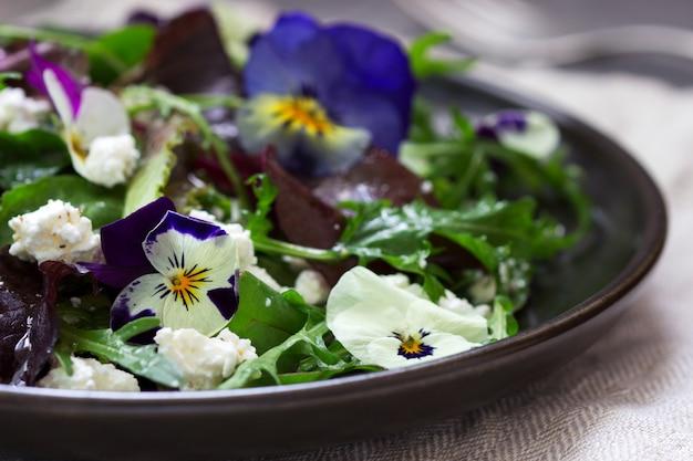Salade van viooltjes en kruiden op smaak gebracht met plantaardige olie, citroensap en kruiden.