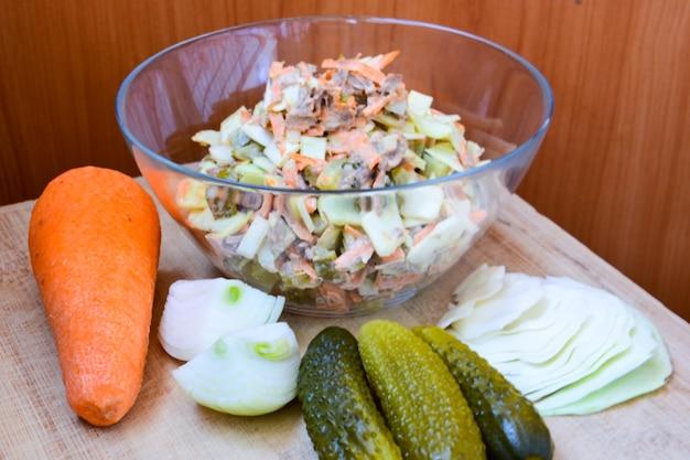 Salade van vitaminekool, wortelen, uien, ingelegde komkommer, rundvlees op houten gezond eten. eigengemaakt.