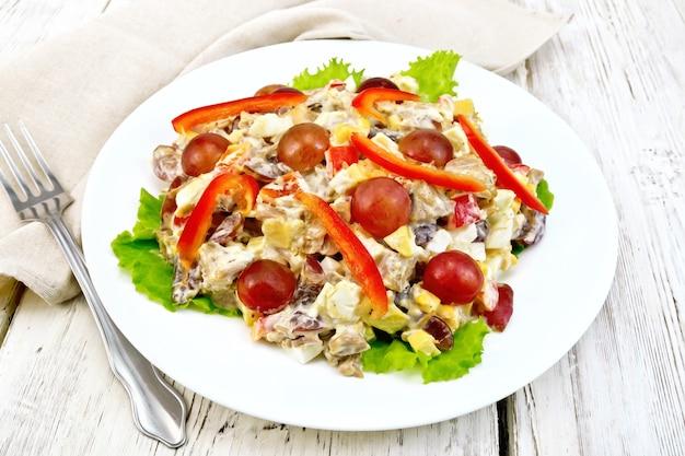 Salade van vlees, zoute zachte fetakaas, paprika, ei en druif met mayonaise op sla de plaat, servet en vork op de achtergrond lichte houten planken