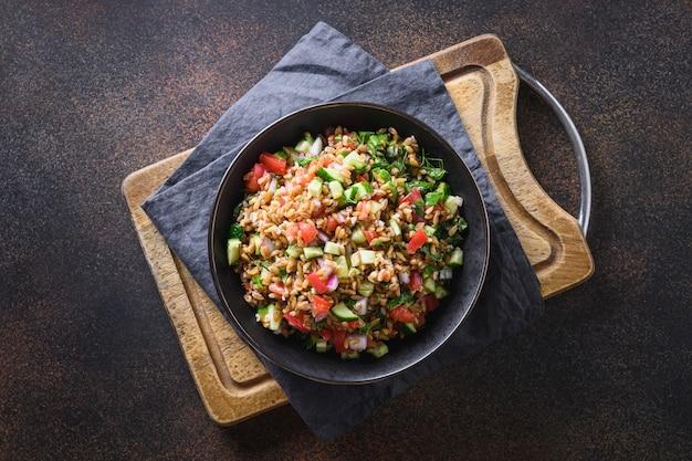 Salade van volkoren granen gespeld met seizoensgroenten, tomaat, komkommer, greens in kom op donker. bovenaanzicht.