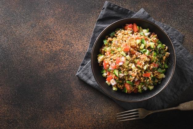 Salade van volkoren granen gespeld met seizoensgroenten, tomaat, komkommer in kom op bruine achtergrond. bovenaanzicht. kopieer ruimte.