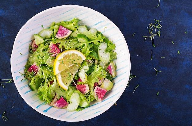 Salade van watermeloenradijs, komkommer, selderij en slablaadjes. veganistisch eten. dieetmenu. bovenaanzicht, overhead, kopieerruimte
