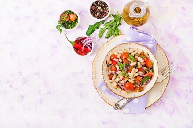 Salade van witte bonen, tomaat, rucola, rode ui en peper in kom.