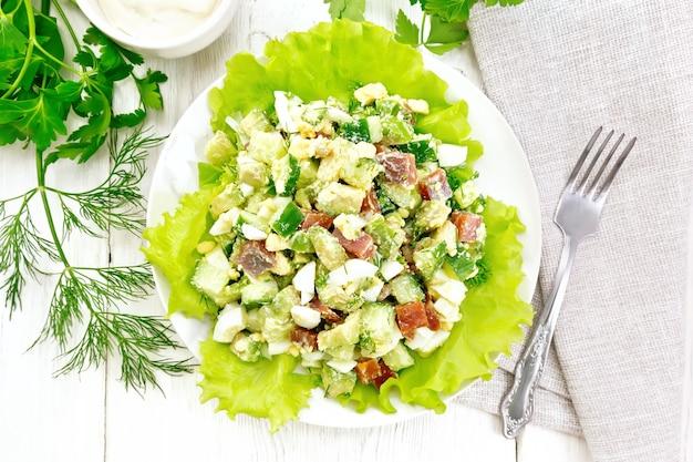 Salade van zalm, komkommer, eieren en avocado met mayonaise op slabladeren in een bord, servet, dille, peterselie en vork op een houten plankachtergrond van bovenaf