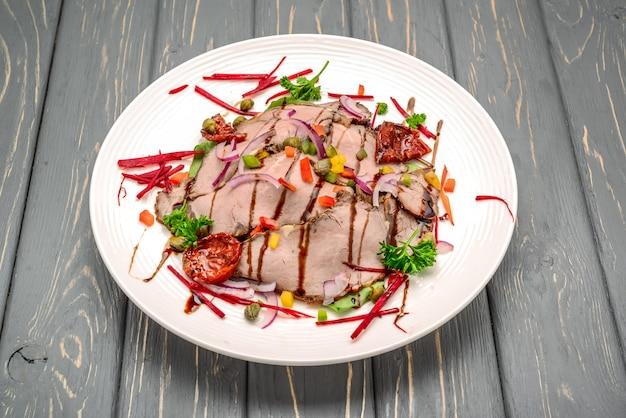 Saladebladeren met gesneden rosbief en in de zon gedroogde cherrytomaten