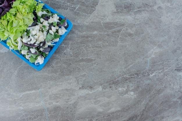 Salademix van bloemkool, kool en amarant op een blauwe schaal op marmer.