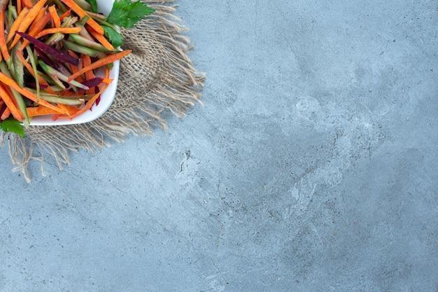 Salademix van gesneden wortelen, rode biet en komkommers in een kom op marmeren ondergrond