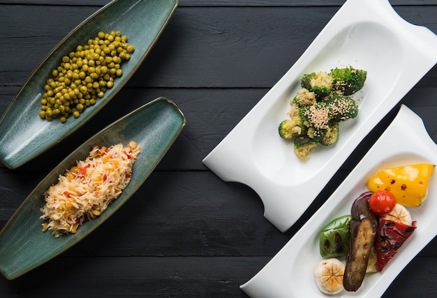 Salades en plantaardig voedsel in borden op een zwarte houten ondergrond