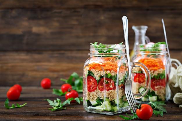 Salades met quinoa, rucola, radijs, tomaten en komkommer in glazen potten op houten tafel. gezonde voeding, dieet, detox en vegetarisch concept