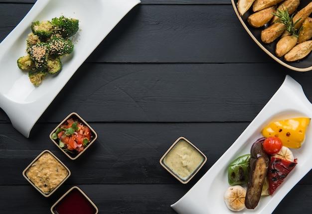 Salades, plantaardig voedsel en jus in borden op een zwarte houten ondergrond