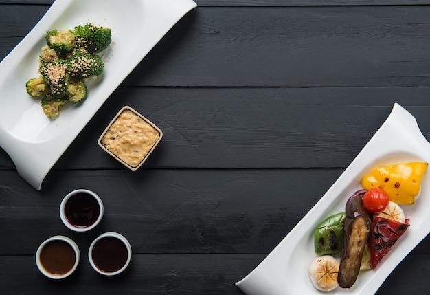 Salades, plantaardig voedsel en sauzen in borden op een zwarte houten ondergrond