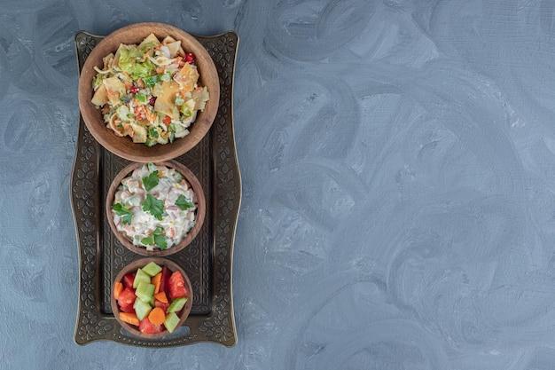 Salades van gemengde groenten, olivier en herder in houten kommen op een dienblad op marmeren tafel.