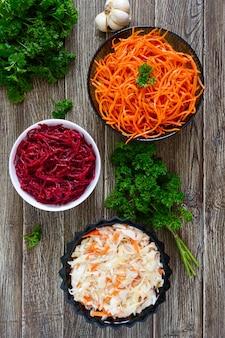 Salades van verse groenten: kool, wortelen, bieten. koreaanse pittige salades in kommen op een houten tafel. bovenaanzicht. vitamine menu. veganistische keuken.