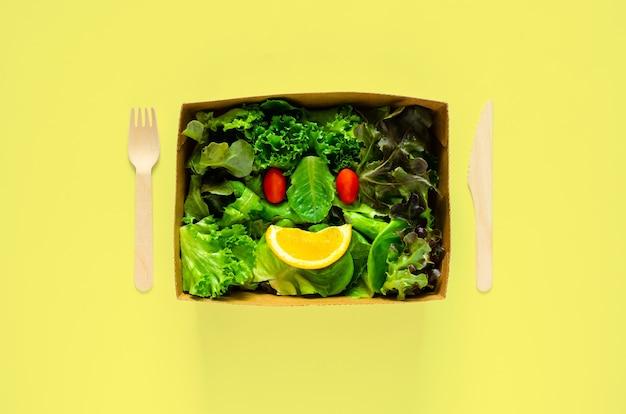 Saladeset als glimlachgezicht zet in wegwerpbare, composteerbare papieren voedseldoos, vork en lepel op gele achtergrond voor wereldmilieudagconcept