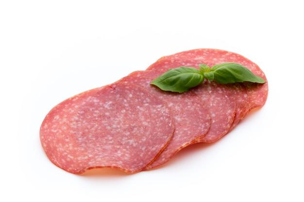 Salami gerookte worstplakken die op wit oppervlakte knipsel worden geïsoleerd.