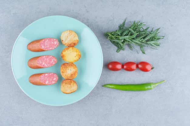 Salami met gebakken aardappelen op blauw bord met groenten.
