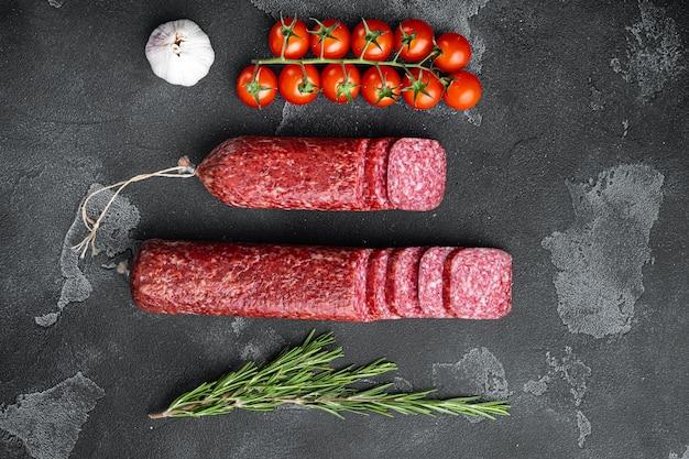 Salami met ingrediëntenset, op zwarte donkere stenen tafel, bovenaanzicht plat gelegd