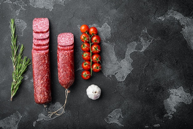Salami met kruiden en specerijen set, op zwarte donkere stenen tafel, bovenaanzicht plat gelegd