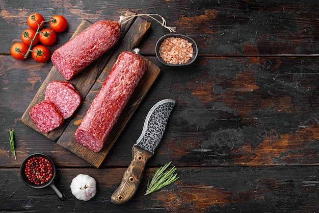 Salami met kruiden, knoflookset, op oude donkere houten tafel, bovenaanzicht plat gelegd