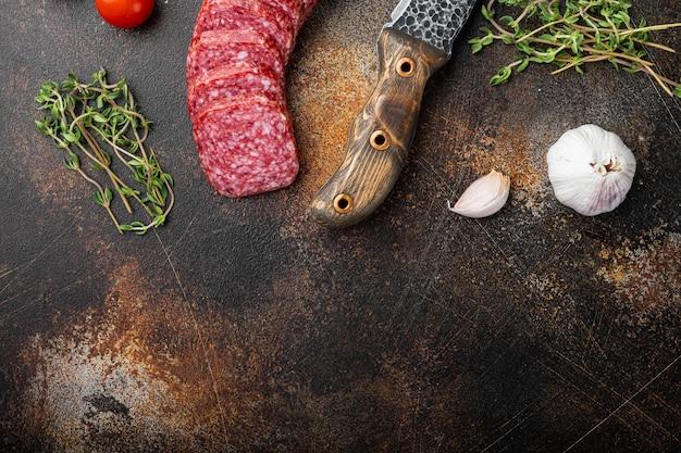 Salami met kruiden, knoflookset, op oude donkere rustieke tafel, bovenaanzicht plat gelegd