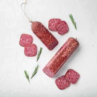 Salami met kruiden, knoflookset, vierkant formaat, op witte stenen tafel, bovenaanzicht plat gelegd