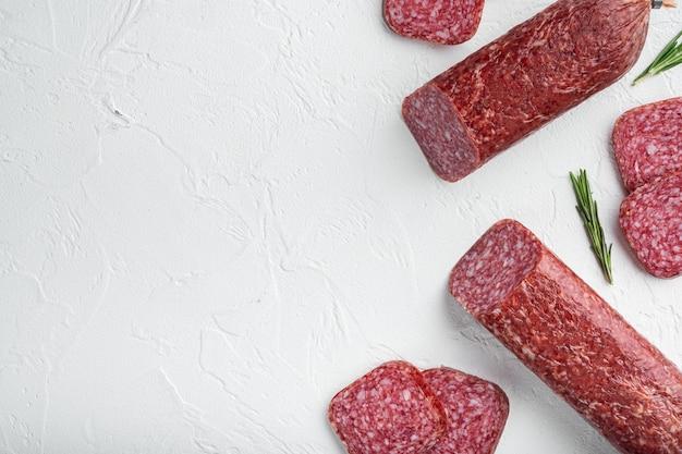 Salami met verse rozemarijn en kruiden set, op witte stenen tafel, bovenaanzicht plat lag