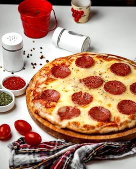 Salami pizza gegarneerd met gedroogde kruiden
