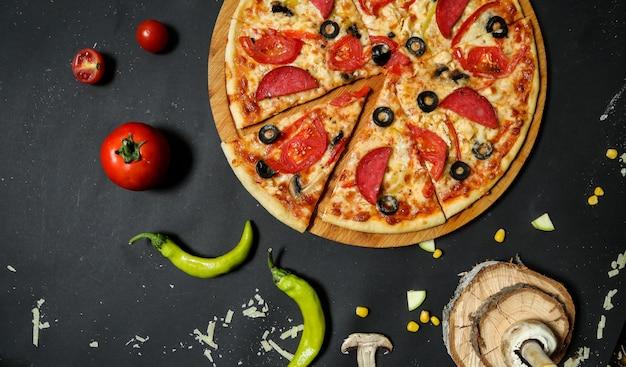 Salami pizza gegarneerd met verse tomaten en olijven plakjes bovenaanzicht