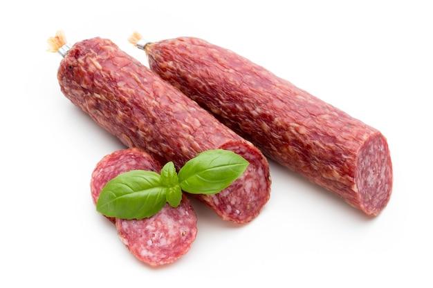 Salami rookworst, basilicumbladeren en peperkorrels geïsoleerd op wit.