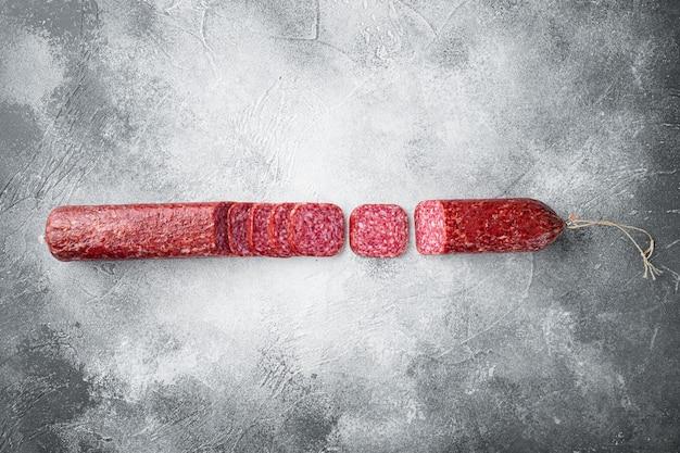 Salami, salami rookworst, gesneden set, op grijze stenen tafel, bovenaanzicht plat gelegd