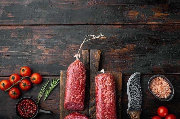 Salami, salami rookworst, gesneden set, op oude donkere houten tafel, bovenaanzicht plat gelegd