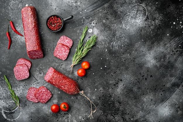 Salami, salami rookworst, gesneden set, op zwarte donkere stenen tafel, bovenaanzicht plat gelegd