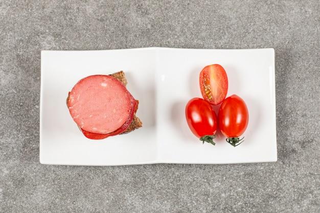 Salamisandwich en verse tomaat op witte plaat over grijs.