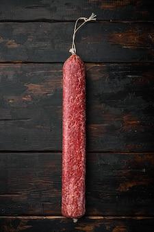Salamiworstset, op oude donkere houten tafel, bovenaanzicht plat gelegd