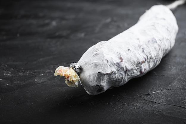 Salchichon, spaanse salamiworst op zwarte achtergrond.
