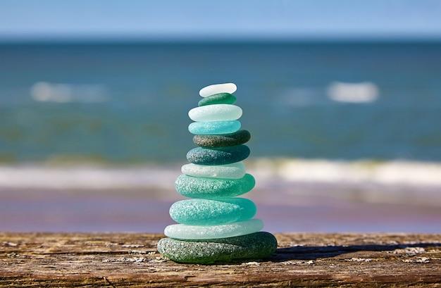 Saldo van stenen. glazen stenen op een houten tafel tegen de zee