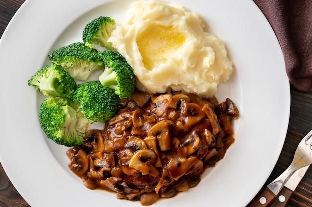 Salisbury steak gegarneerd met aardappelpuree en broccoli