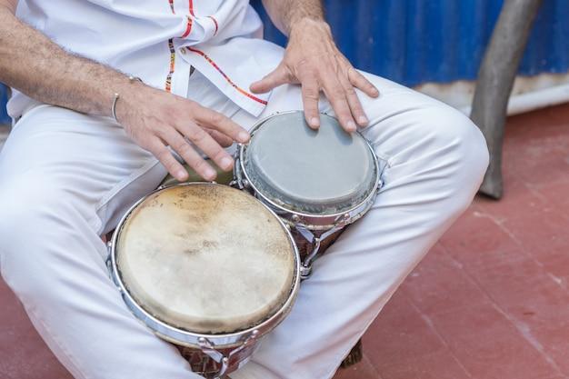 Salsa-muzikant die de bongos speelt, een percussie-instrument dat traditioneel is voor de caribische en latijns-amerikaanse muziek