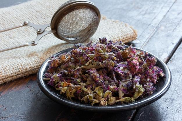 Salvia om kruidenthee te maken op een zwarte schotel en een zeef