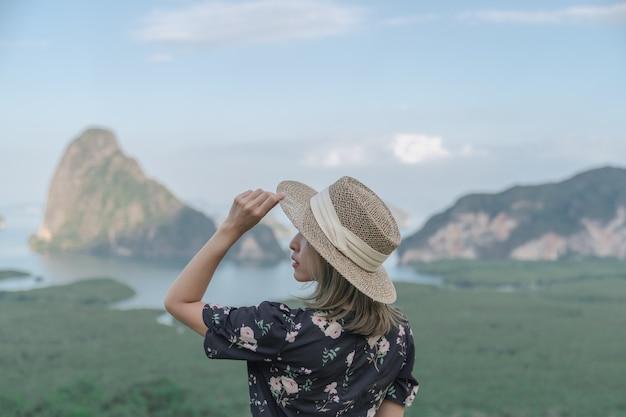 Samed nang chee. vrouw met uitzicht op de baai van phang nga, het mangrovebos en de heuvels aan de andamanzee, thailand.