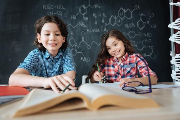 Samen aantekeningen maken. geamuseerde positief geschoolde kinderen die op school zitten en genieten van de les terwijl ze aan het project werken en aantekeningen maken