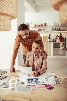 Samen creëren. geconcentreerde knappe modeontwerper en zijn mooie assistent werken aan hun nieuwe collectie.