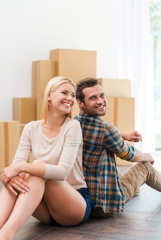 Samen een nieuw leven beginnen. gelukkig jong stel zittend op de vloer van hun nieuwe appartement terwijl kartonnen dozen op de achtergrond liggen