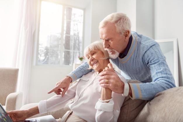Samen een reis plannen. aangename senior man die zijn geliefde vrouw van achteren knuffelt en naar de laptop wijst terwijl ze de kaart online bekijken en hun jubileumreis plannen