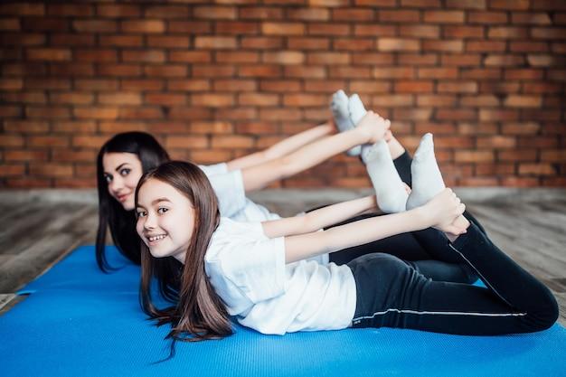 Samen een rustige omgeving houden. twee vreedzame jonge zussen die zich uitstrekken en ontspannen in het yogacentrum.