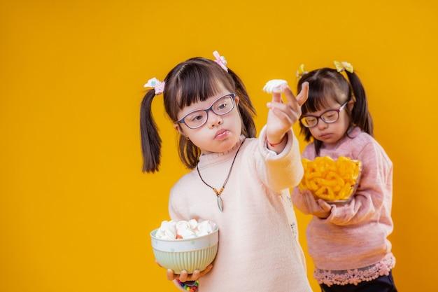 Samen eten. twee schattige kinderen met het syndroom van down die lekkere snacks dragen en ze laten zien