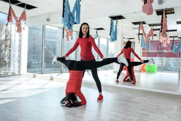 Samen fit meisje trainen. portret van twee geschikte jonge vrouwen die op fitness in de lichte gymnastiek uitoefenen