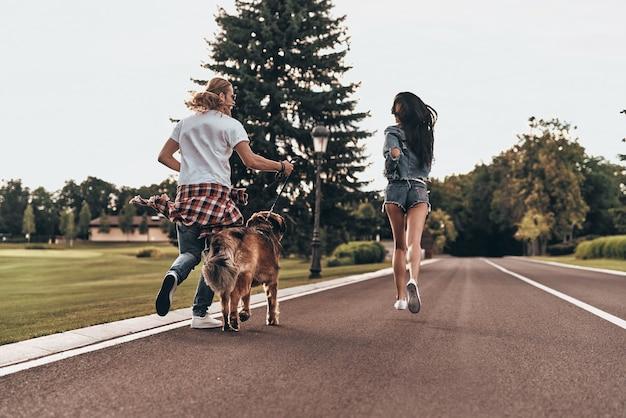 Samen gek worden. achteraanzicht van de volledige lengte van een mooi jong stel dat met hun hond rent terwijl ze tijd buitenshuis doorbrengen