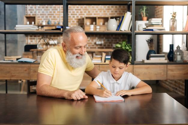 Samen gemakkelijker. vrolijke oudere man zit aan de tafel naast zijn kleinzoon van de pre-tiener en hem te helpen met de toewijzing van school thuis